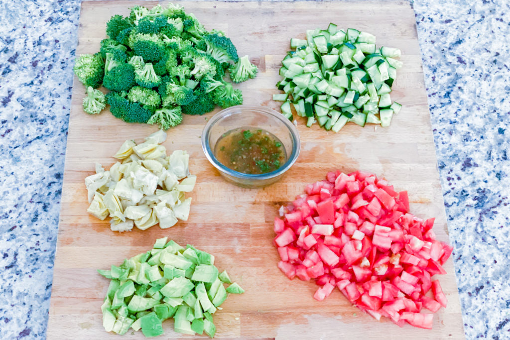 Cutting board with chopped cucumbers, tomatoes, artichokes, avocados, and broccoli.