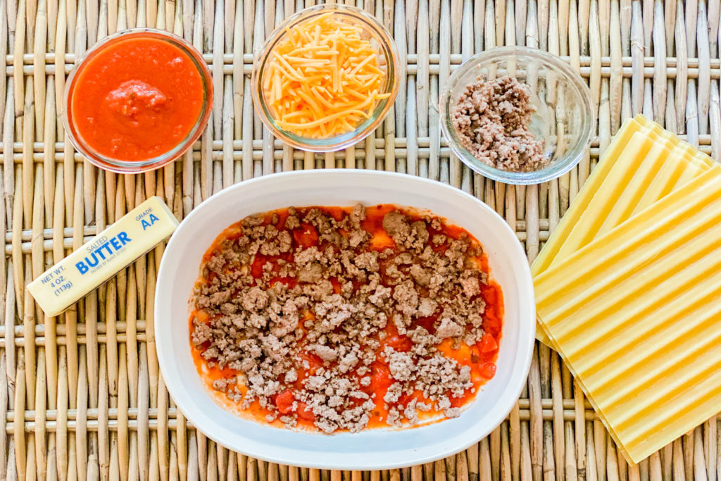 Ground beef being layered on top of pasta sauce.