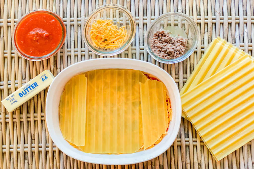 Delverde noodles being layered on top of the cheddar cheese, ground beef, and pasta sauce