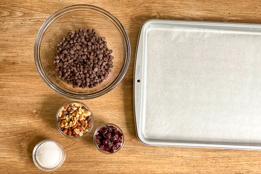Chocolate chips in a bowl with bowls of nuts, craisins and salt. Baking sheet with waxed paper