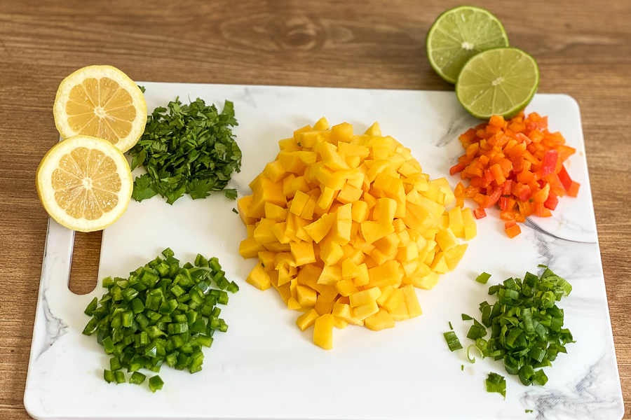 Mangoes, jalapeno, bell pepper and cilantro on a cutting board