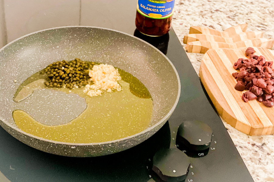 A sauce pan with capers, garlic, and olive oil.