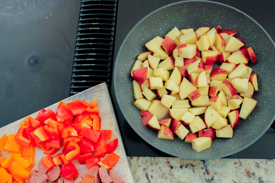 A skillet on a stove top with diced potatoes next to a cutting board with diced bell peppers and kielbasa.