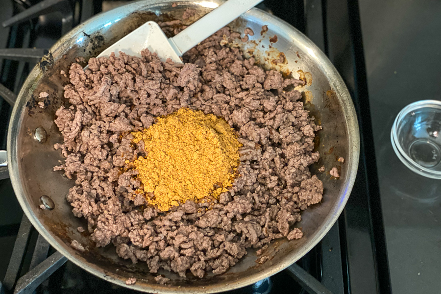 Browned ground beef on the stove with taco seasoning