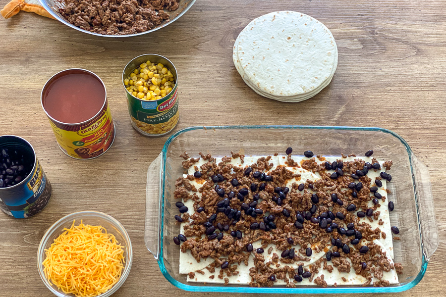 Ground beef and black beans spread over tortillas in a baking dish