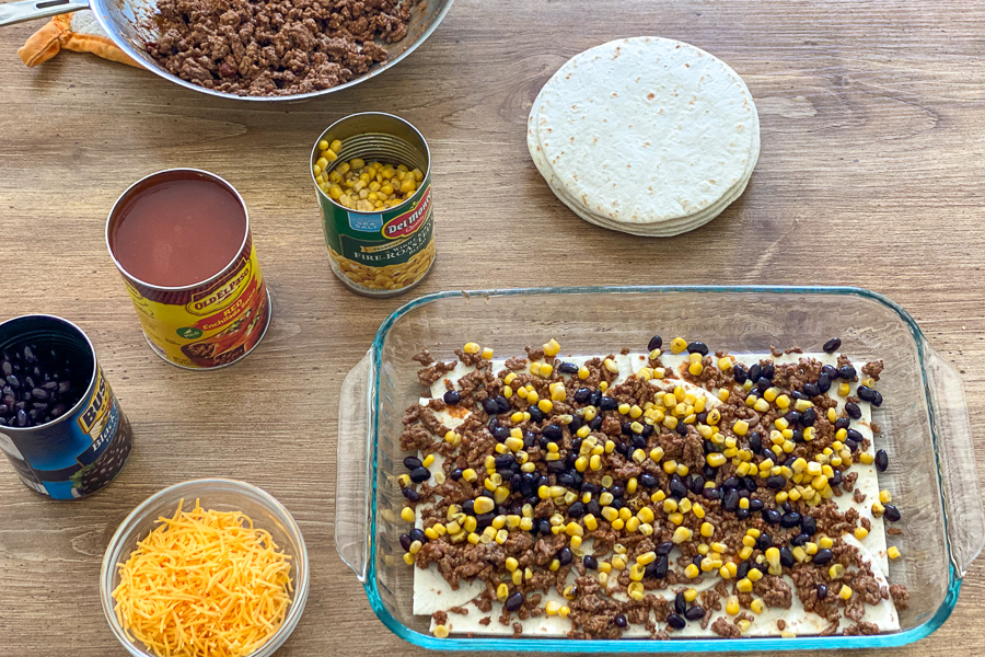 Ground beef, black beans, and corn spread over tortillas in a baking dish