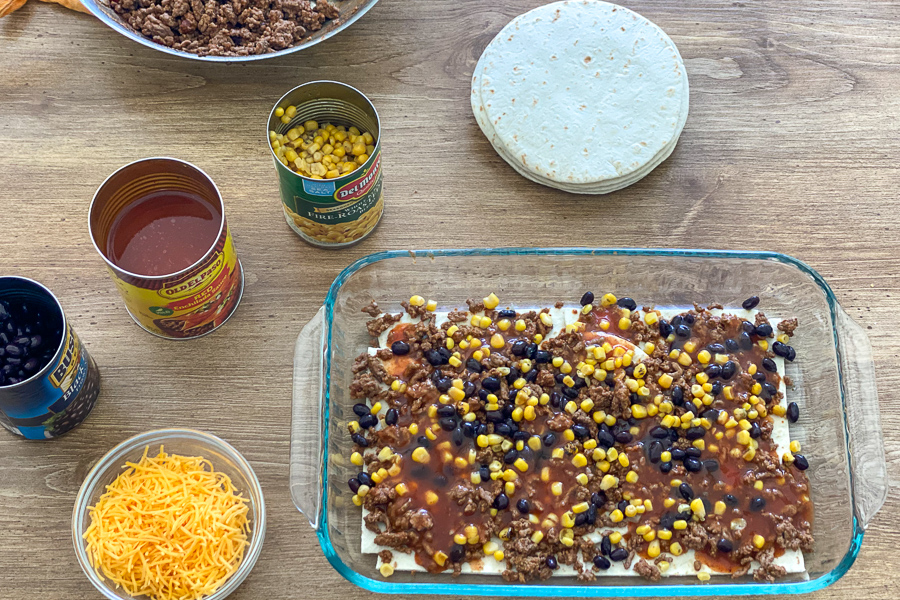Ground beef, black beans, and corn spread over tortillas in a baking dish with enchilada sauce poured over top