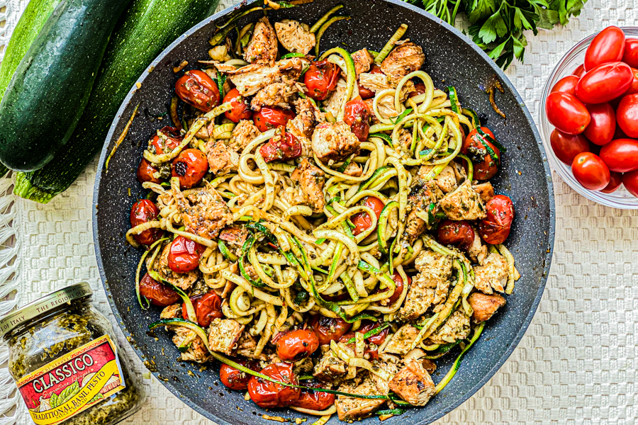 The final dish of our One Pan Chicken Zoodles in a skillet next to whole zucchini, a jar of pesto and a bowl of cherry tomatoes.