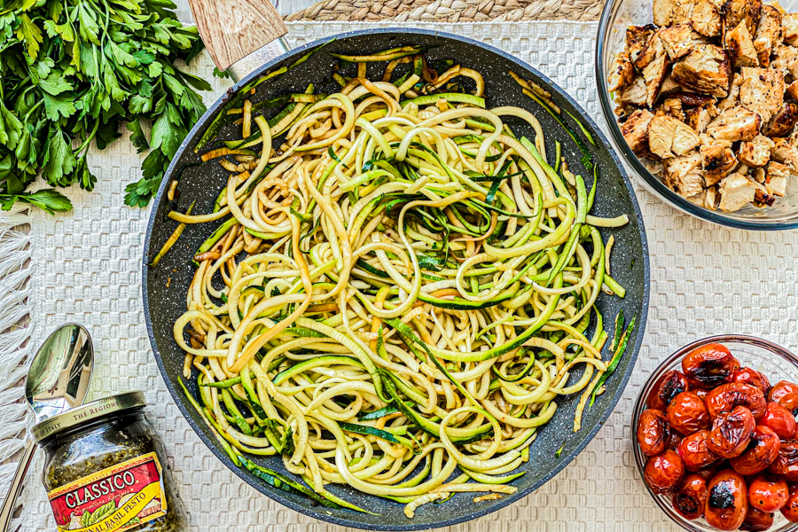 Zoodles in a skilled surrounded by cooked, diced chicken, charred tomatoes, and a jar of pesto.
