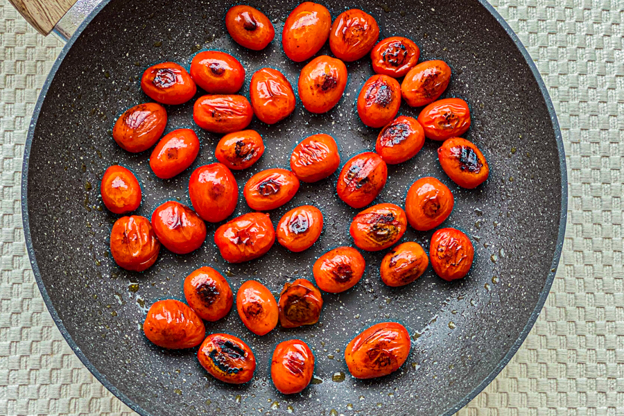 Cherry tomatoes in a skillet being charred.