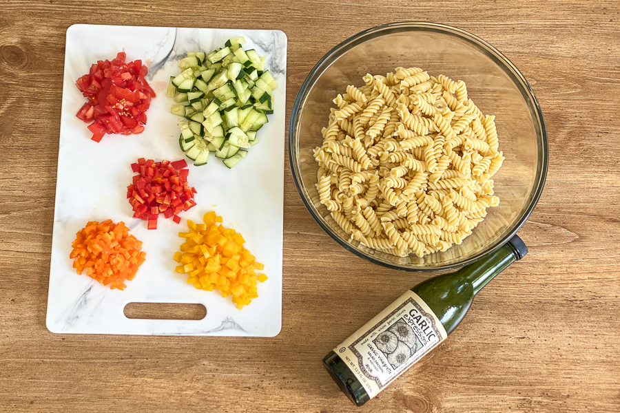 Vegetables on a cutting board with a bowl of pasta and a bottle of salad dressing