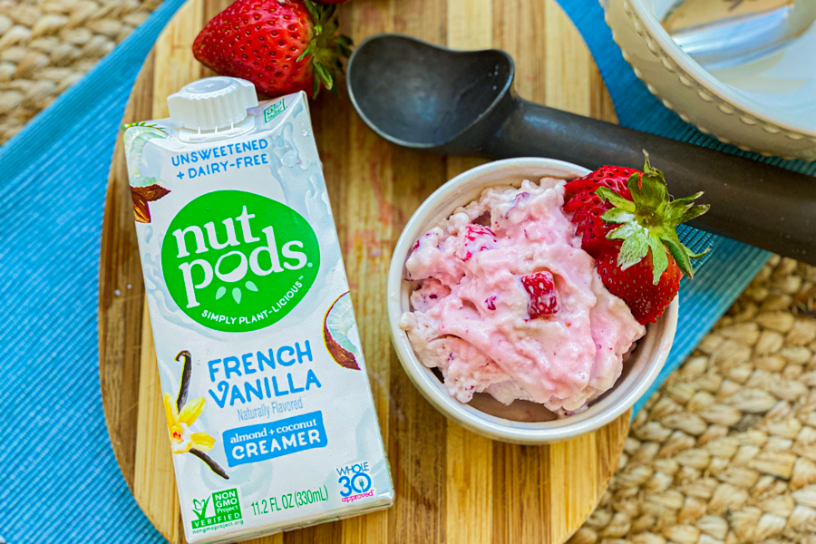 A bowl of strawberry ice cream on a board with nutpods creamer next to it.