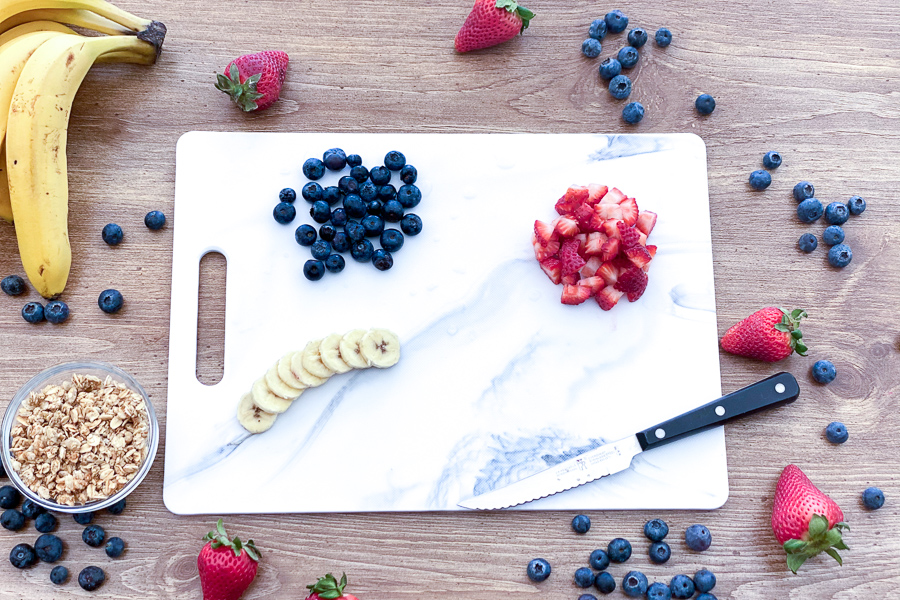 Diced strawberries, blueberries and sliced banana on a cutting board with a knife with fruit all around