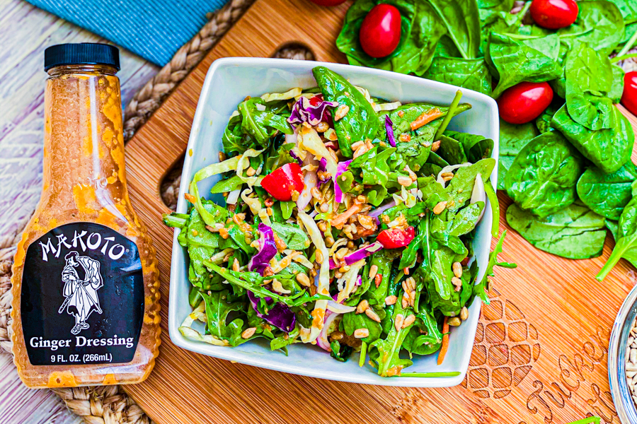 Our Asian Spinach Salad in a white bowl on a cutting board next to a bottle of Makoto Ginger Dressing.