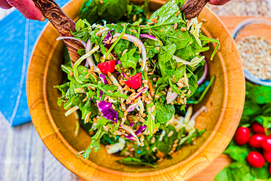 Someone lifting a spoon full of our Asian Spinach Salad up to serve in a small bowl.