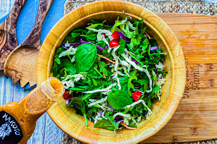 A bowl of our Asian Spinach Salad with someone about to pour the ginger dressing on top.
