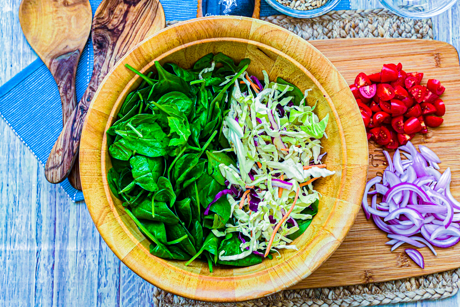 A wooden salad bowl with spinach, chopped cabbage and arugula in it next to chopped red onions and cherry tomatoes.