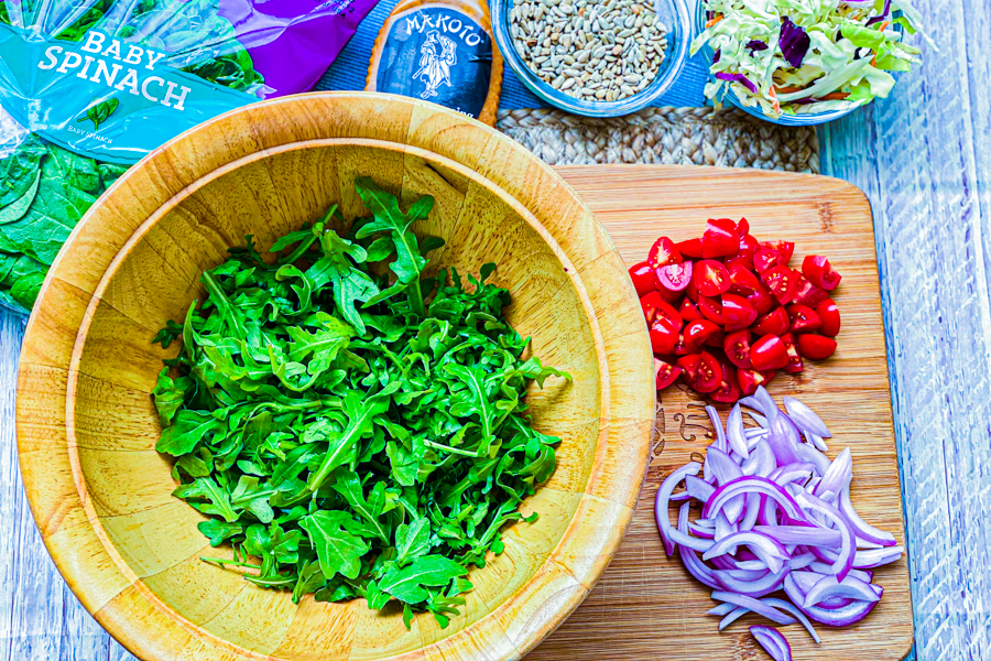 A wooden bowl with arugula in the bottom next to chopped red onions and chopped cherry tomatoes.