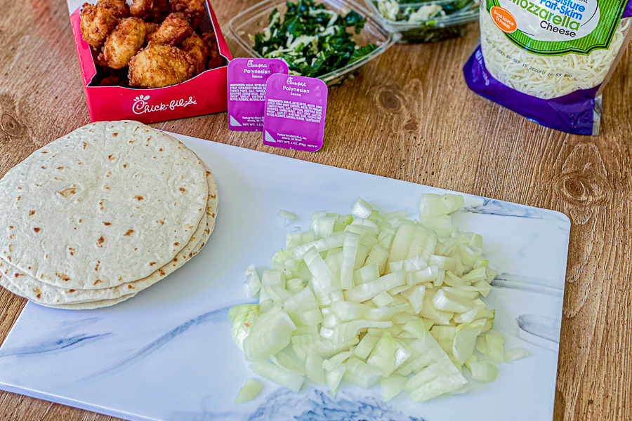 DIced onions on a cutting board with tortillas and ingredients for tacos.