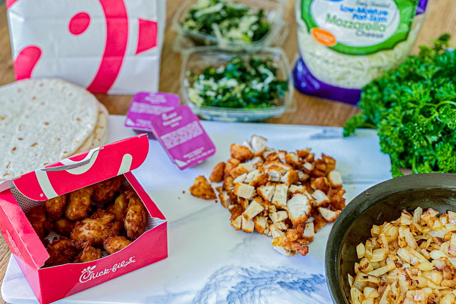 Diced chicken nuggets on cutting board with sauteed onions and box of chicken nuggets. Tortillas, Kale salad, sauce and cheese in background.