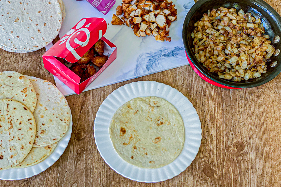Warmed up tortilla on a plate with ingredients for Tacos in background