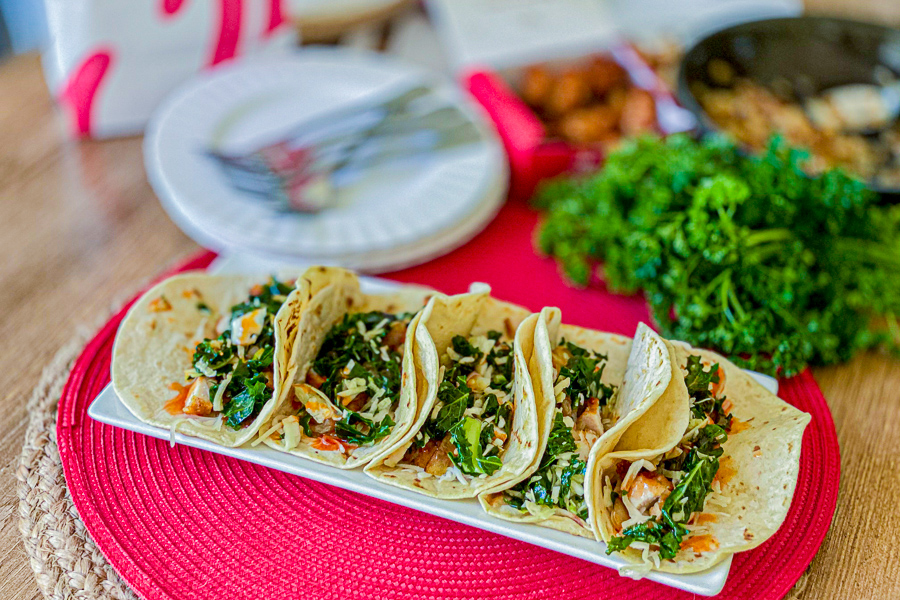 5 Chick Fil A Tacos on a rectangle plate with chicken, onion and plates in the background.