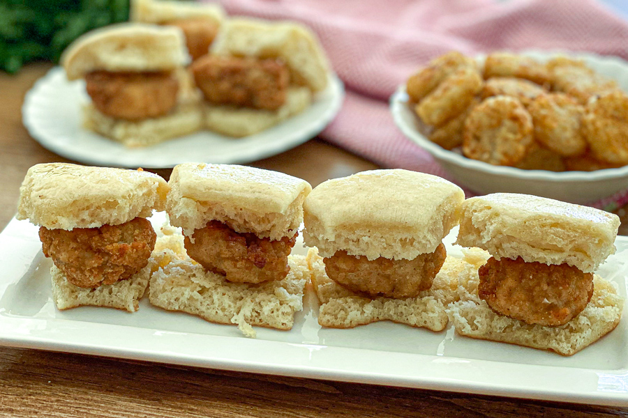 Mini Chicken Biscuits on a plate with biscuits and hashbrowns in the background