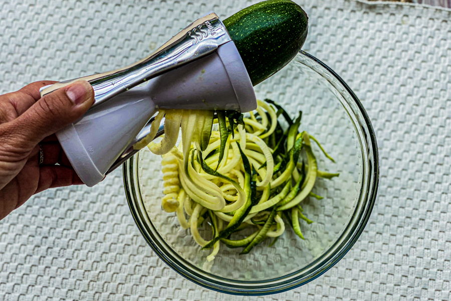 A hand holding a handheld zoodler, making zoodles over a bowl.