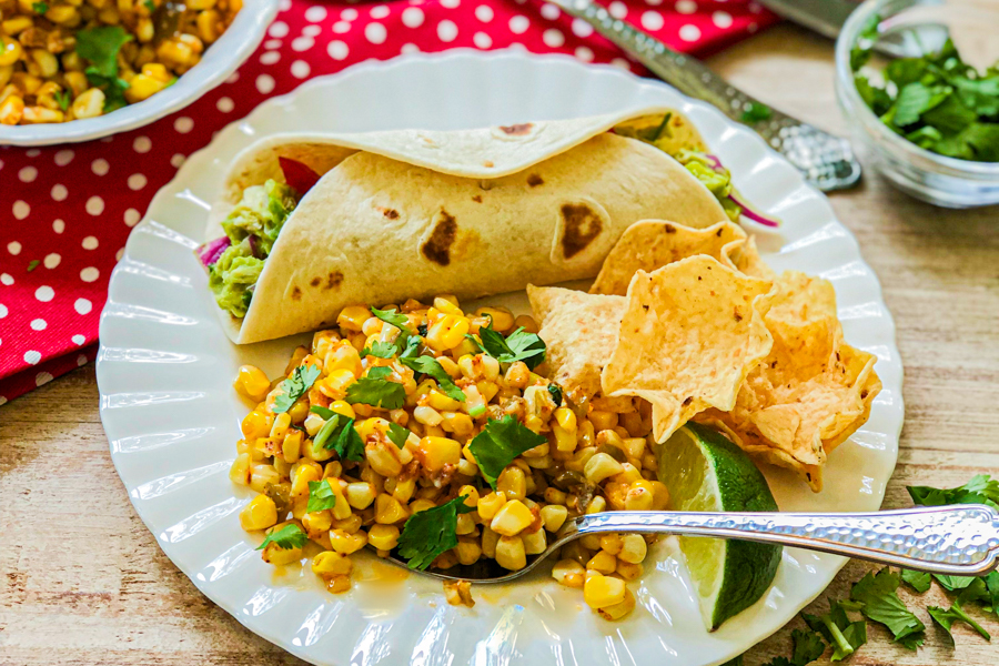 A white plate with our Roasted Street Corn Salad next to a lime wedge, tortilla chips and a taco with guacamole chicken salad inside.