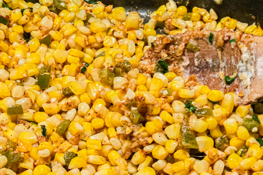 A skillet with corn, cheese, jalapenos in it being mixed by a wooden spoon.