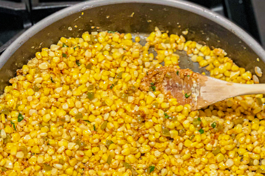 A skillet with corn and jalapenos in it being mixed by a wooden spoon.