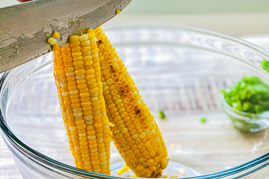 Someone cutting the kernels of corn of the cob in a glass bowl.