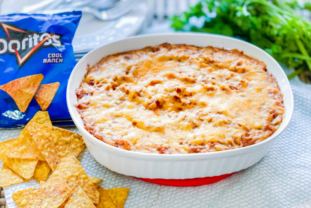 Our Simple Refried Bean Dip after being cooked next to a bag of Dorito chips.