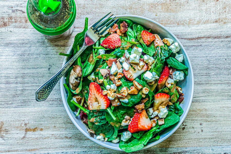 Our Spinach Walnut Feta Salad in a white bowl next to a bottle of salad dressing