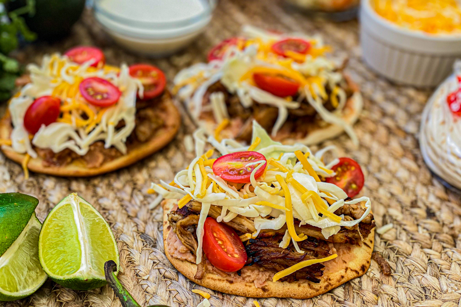 Tostada shell topped with pork, cabbage, cheese, and sliced tomatoes.