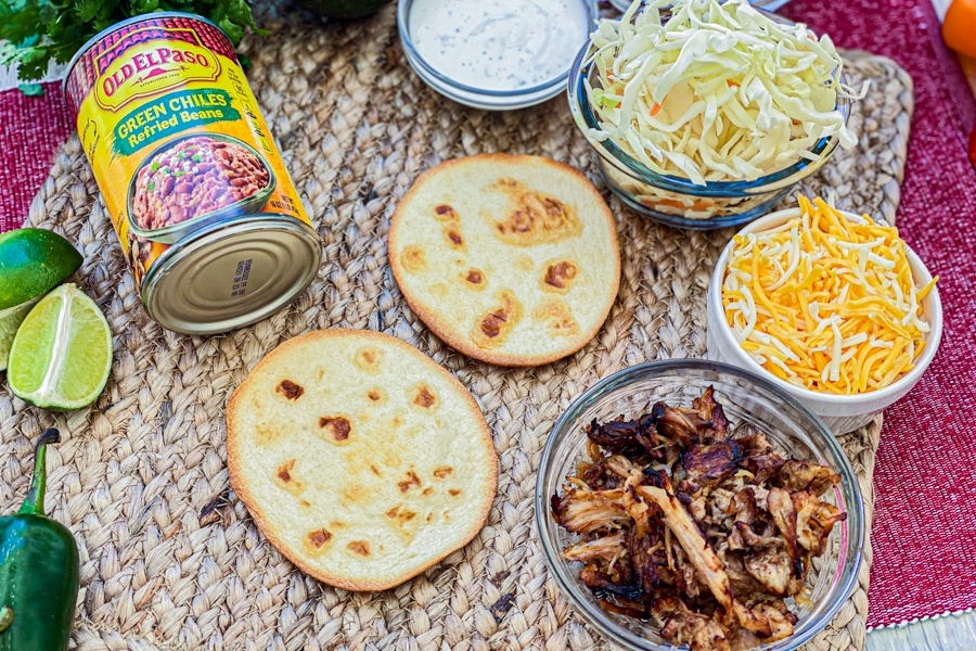 Two tostada shells on a placemat next to a can of refried beans, pork meat, shredded cheese, shredded cabbage, and ranch dressing.