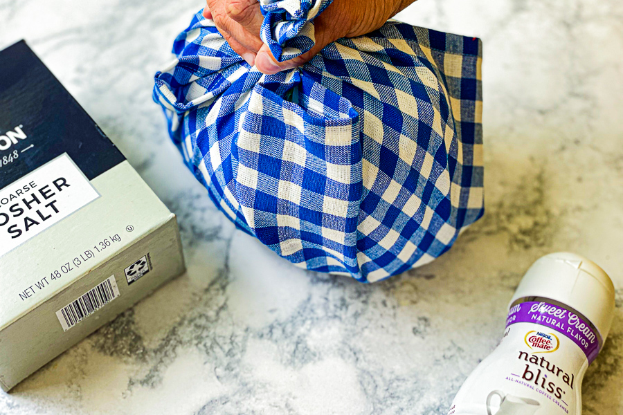 Blue and white dishtowel wrapped around bag of ice ready to shake