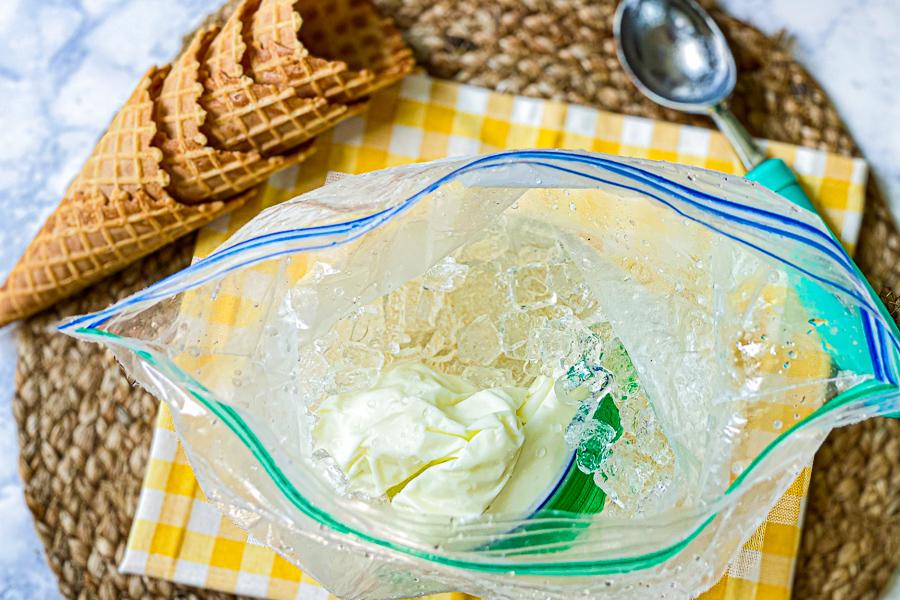 Frozen bag of ice cream in open ziploc bag of ice and salt with waffle cones and ice cream scoop