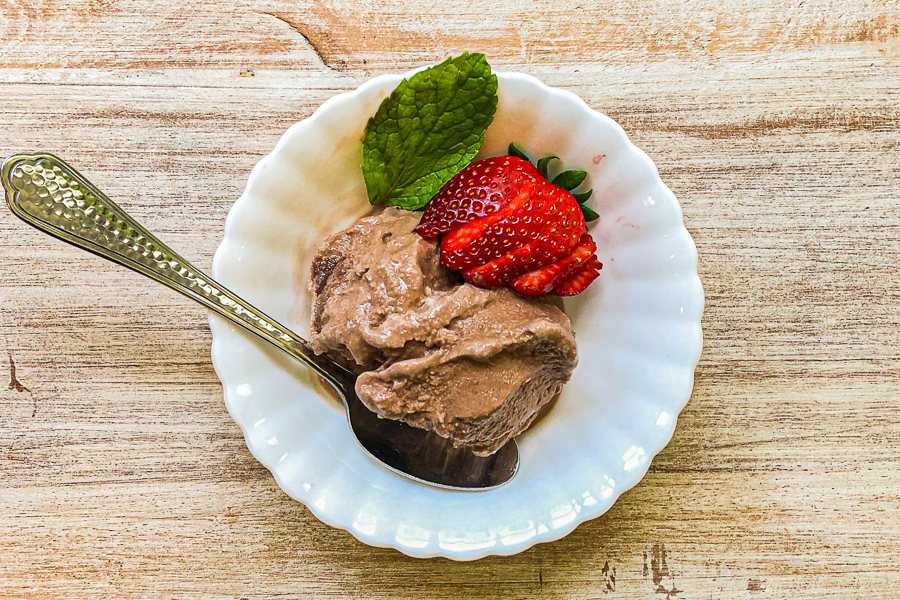 Dairy Free Chocolate Ice Cream in a bowl with strawberry and mint garnish