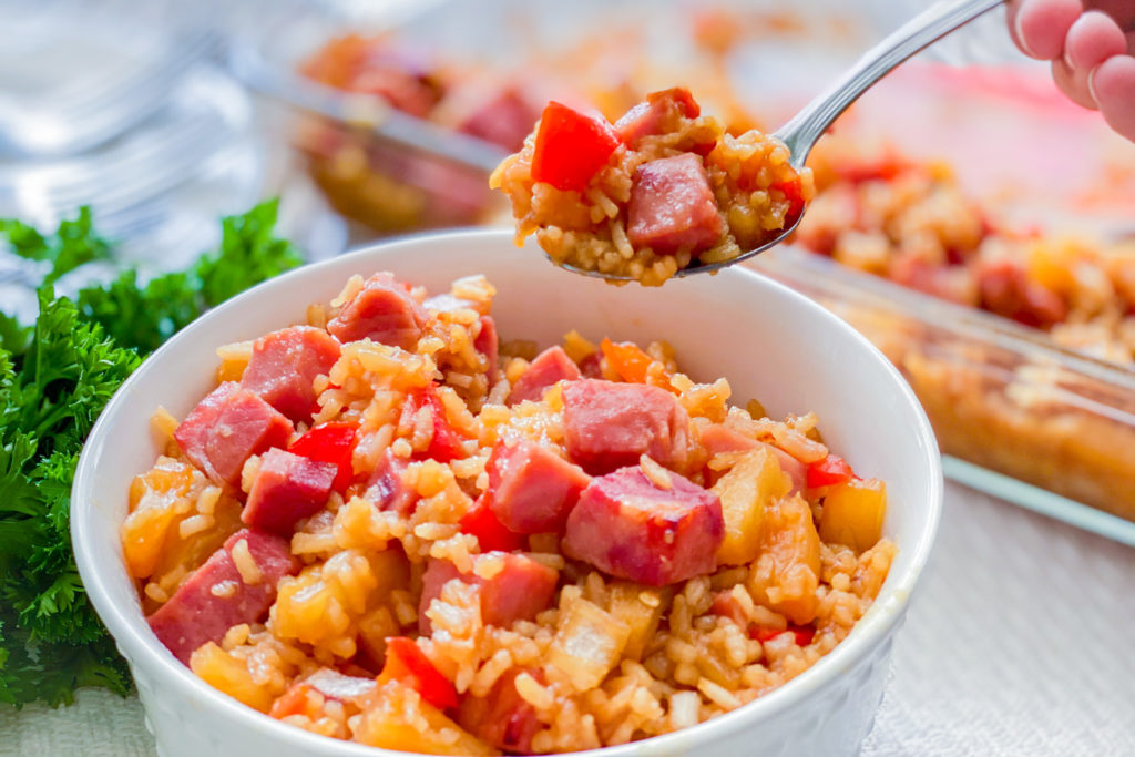 A bowl of our Easiest Ham and Rice Casserole with someone taking a spoonful out.