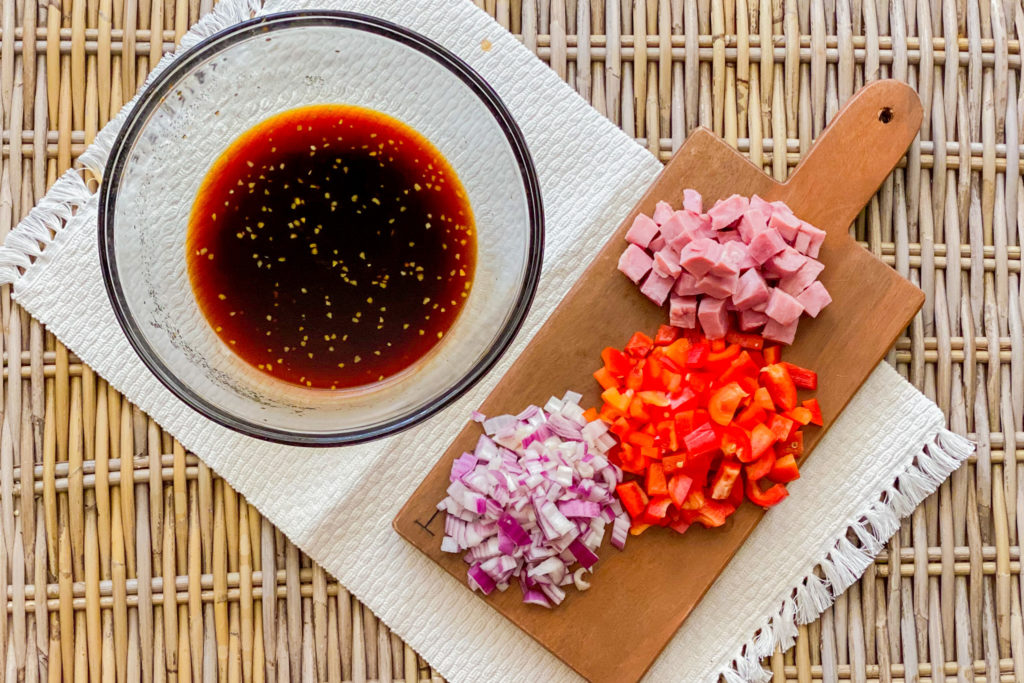 A clear bowl with soy sauce and garlic in it next to a cutting board with chopped red onion, red pepper, and ham.