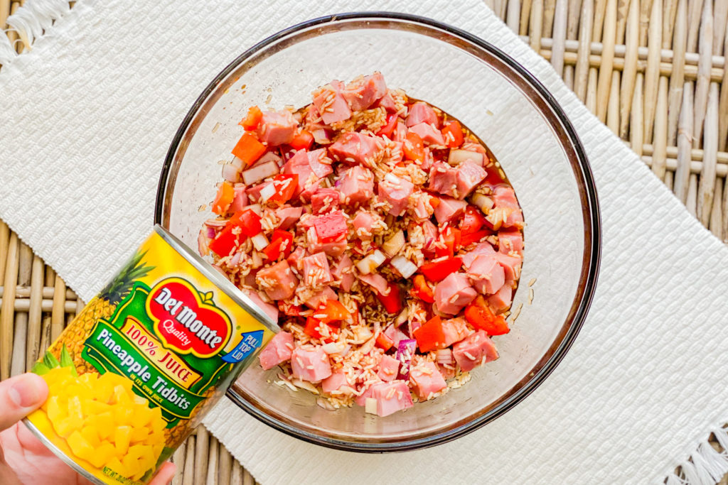 A clear bowl with ham, rice, pepper, onion, and soy sauce with someone pouring in pineapple tidbits from a can.