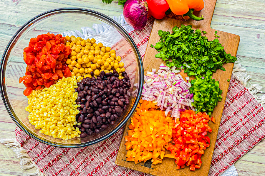A cutting board with diced cilantro, red onion, red and orange bell pepper and jalapeno next to a bowl full of Rotel, chick peas, black beans, and white shoepeg corn.