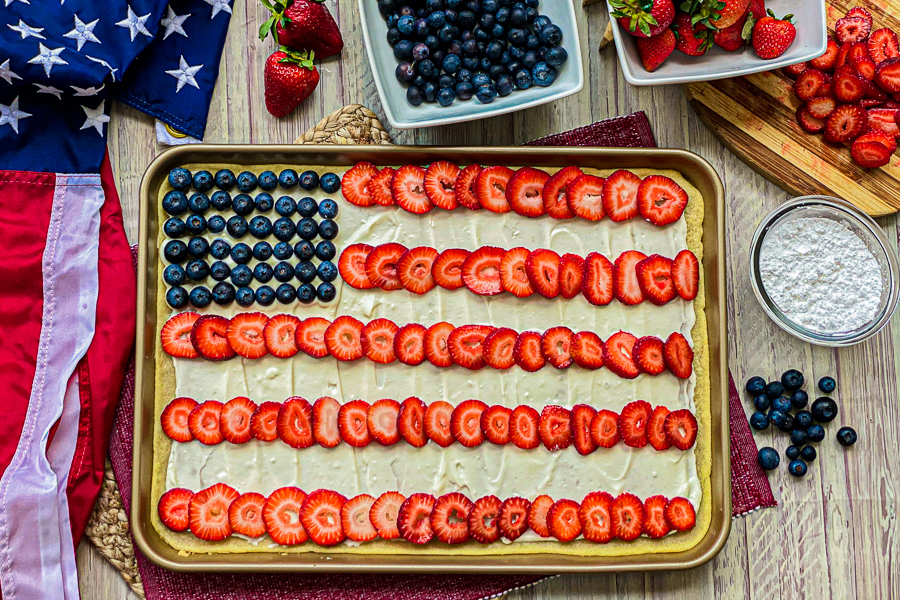 Sugar Cookie Flag Fruit pizza on a table with berries and patriotic decorations.