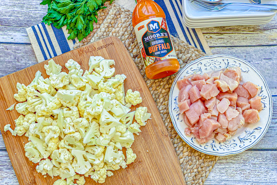 Chopped cauliflower florets on a cutting board next to raw diced chicken and buffalo sauce.