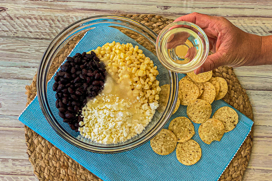 Pouring oil into bowl of black beans, corn and feta