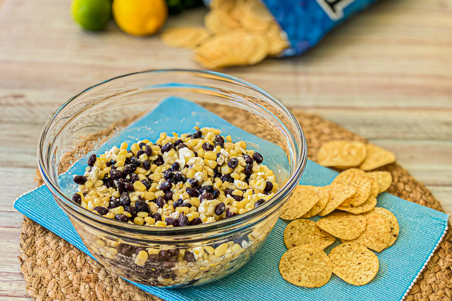 Corn Feta and Black Bean Dip in a bowl with tortilla chips