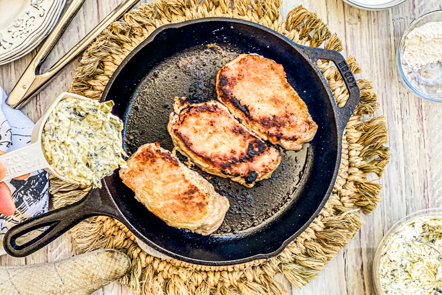 Toasted pork chops after being cooked for 10 minutes with artichoke dip being added on top.