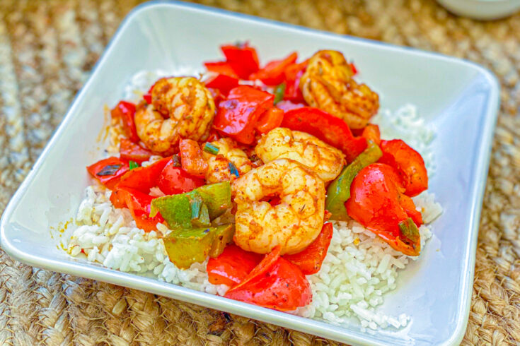 Our Healthy Blackened Shrimp Skillet on some white rice in a white bowl on a table.