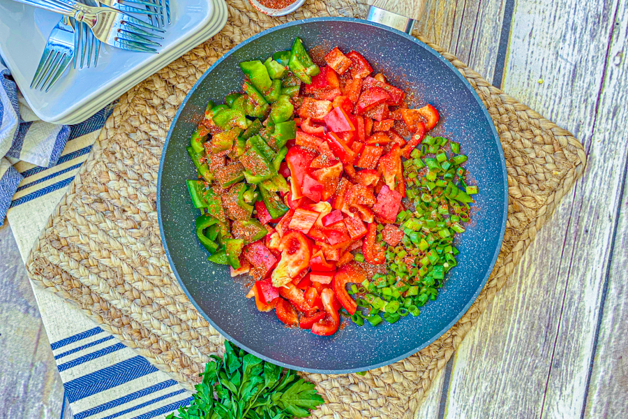Green and red bell peppers and green onions in a skillet with blackening seasoning on top.